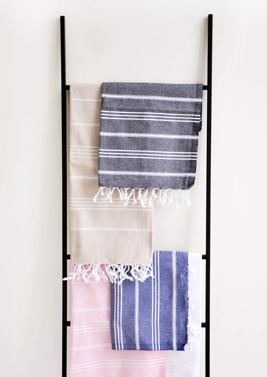 2: Colorful towels with white stripes in a variety of colors hung on a ladder