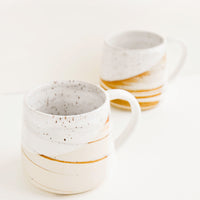 2: Two ceramic mugs with handles in swirled ivory and brown clay with speckled white glazed rim.