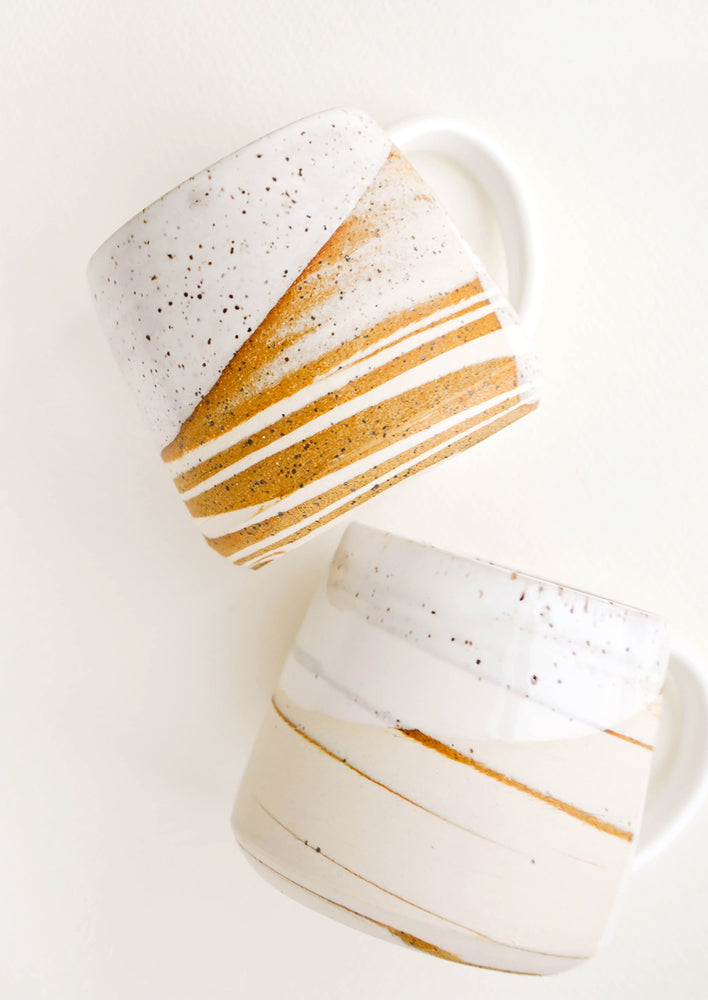 3: Two ceramic mugs with handles in swirled ivory and brown clay with speckled white glazed rim.