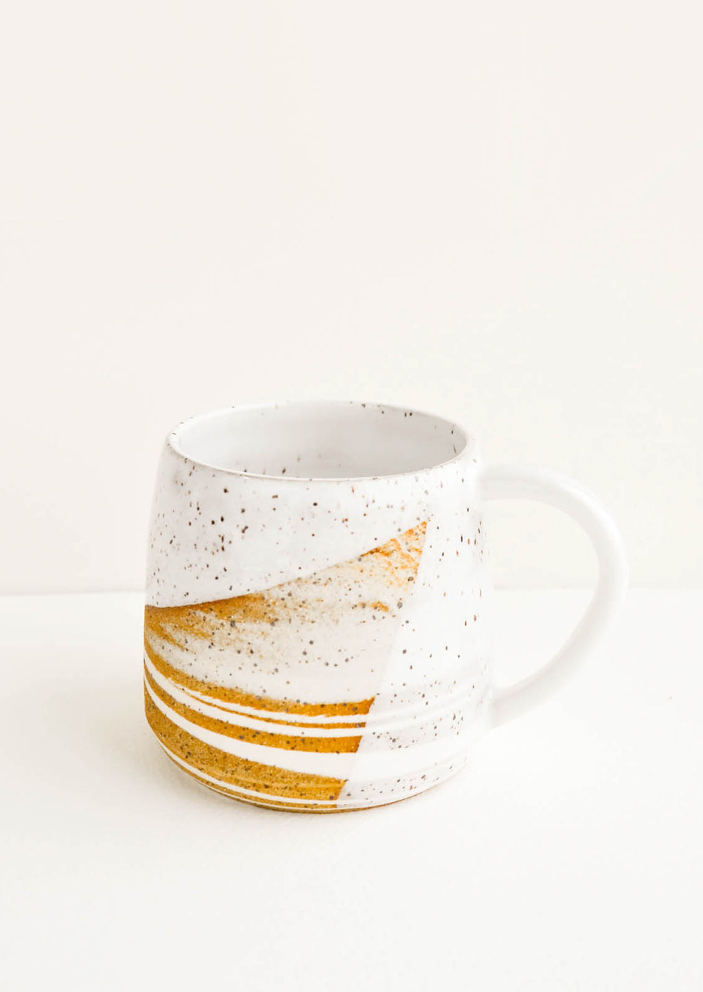 1: A ceramic mug with a handle in swirled ivory and brown clay with speckled white glazed rim.