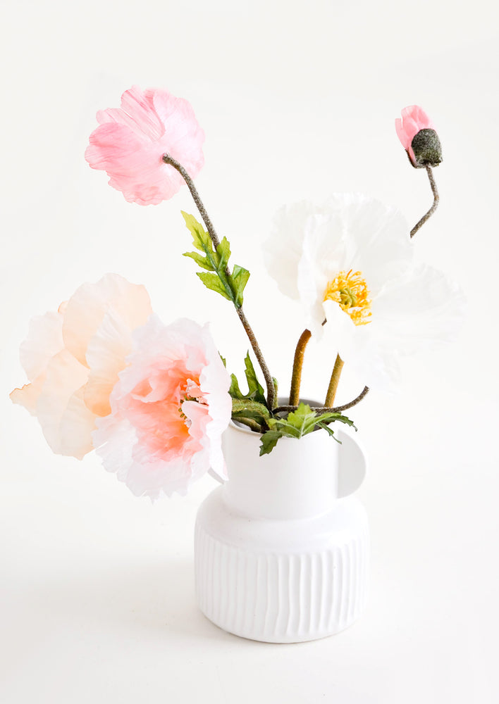 1: Whimsical, white ceramic vase with ribbed texture, pictured with pink flowers