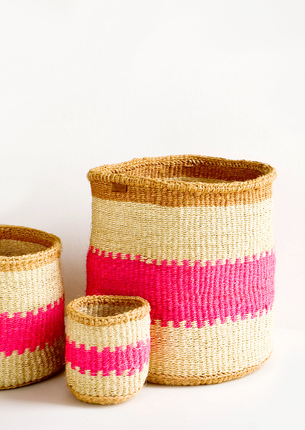 2: Woven sisal baskets in tan stripes with neon pink middle stripe