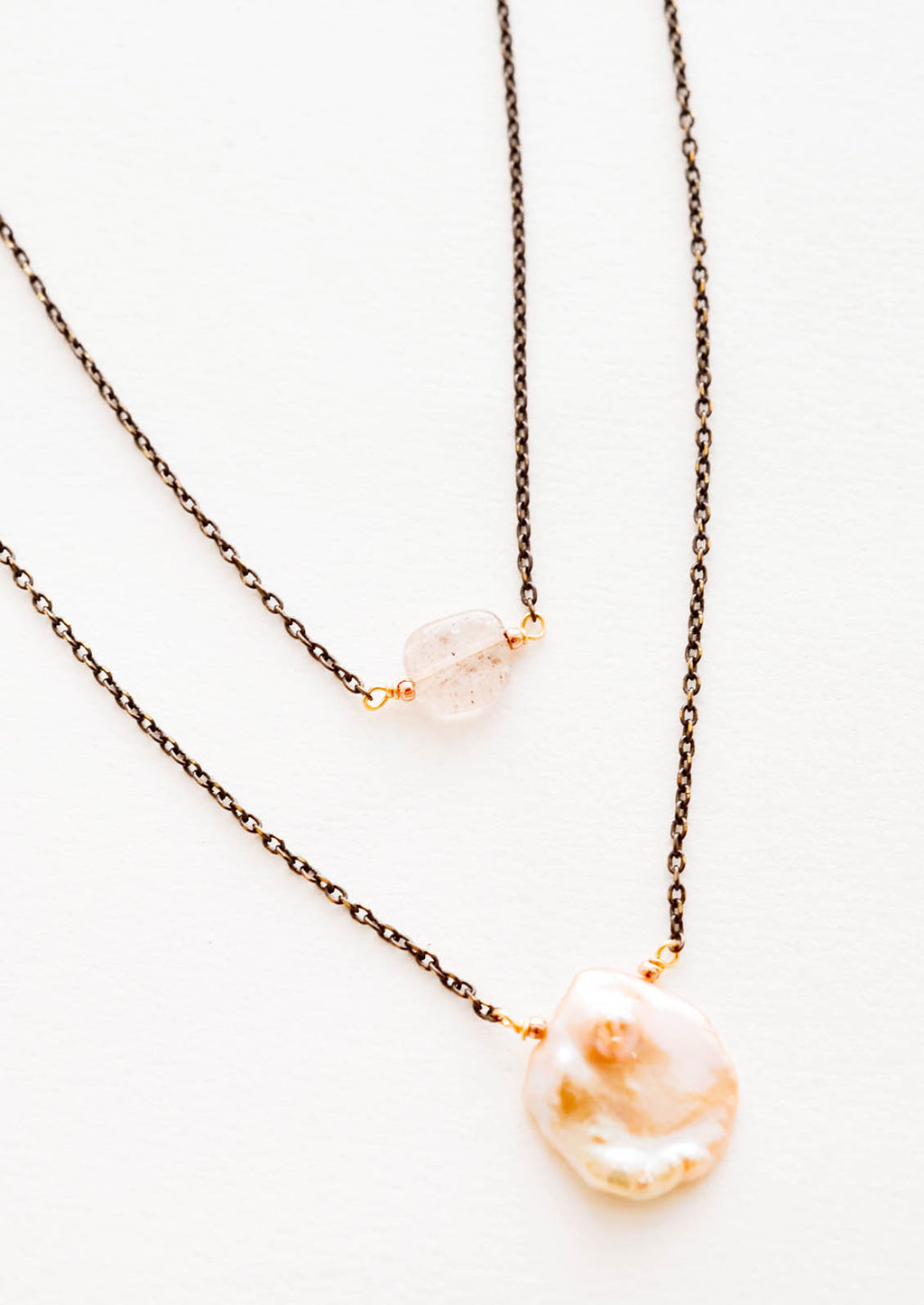 1: Close up of two layer necklace composed of one dark gold chain with translucent pink crystal and one of dark gold chain and pink freshwater pearl.