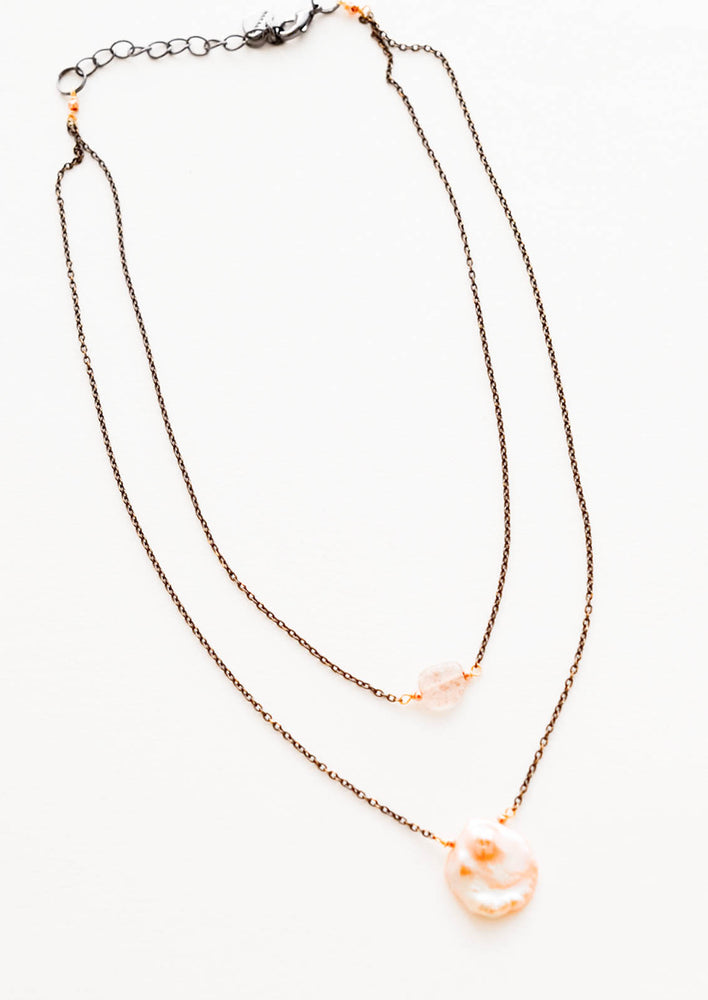 3: Two layer necklace composed of one dark gold chain with translucent pink crystal pendant and one of dark gold chain and pink freshwater pearl pendant.