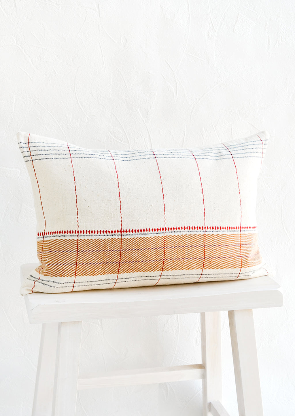 1: Small lumbar throw pillow in natural cotton with contrast embroidery detailing.