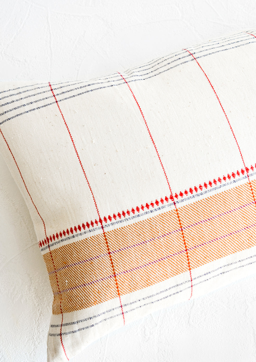 2: Throw pillow with intersecting stripes and embroidery