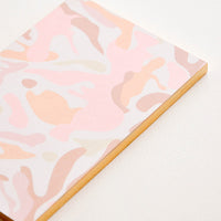 2: Small notebook with pink camouflage pattern decoration.