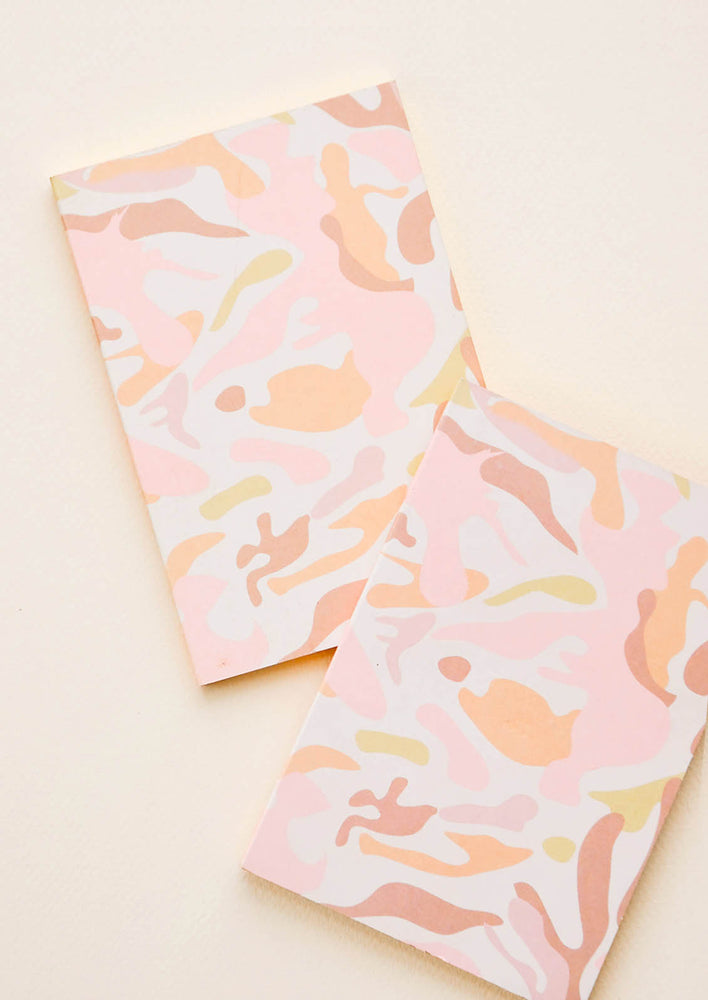 1: Two small notebooks with pink camouflage pattern decoration.