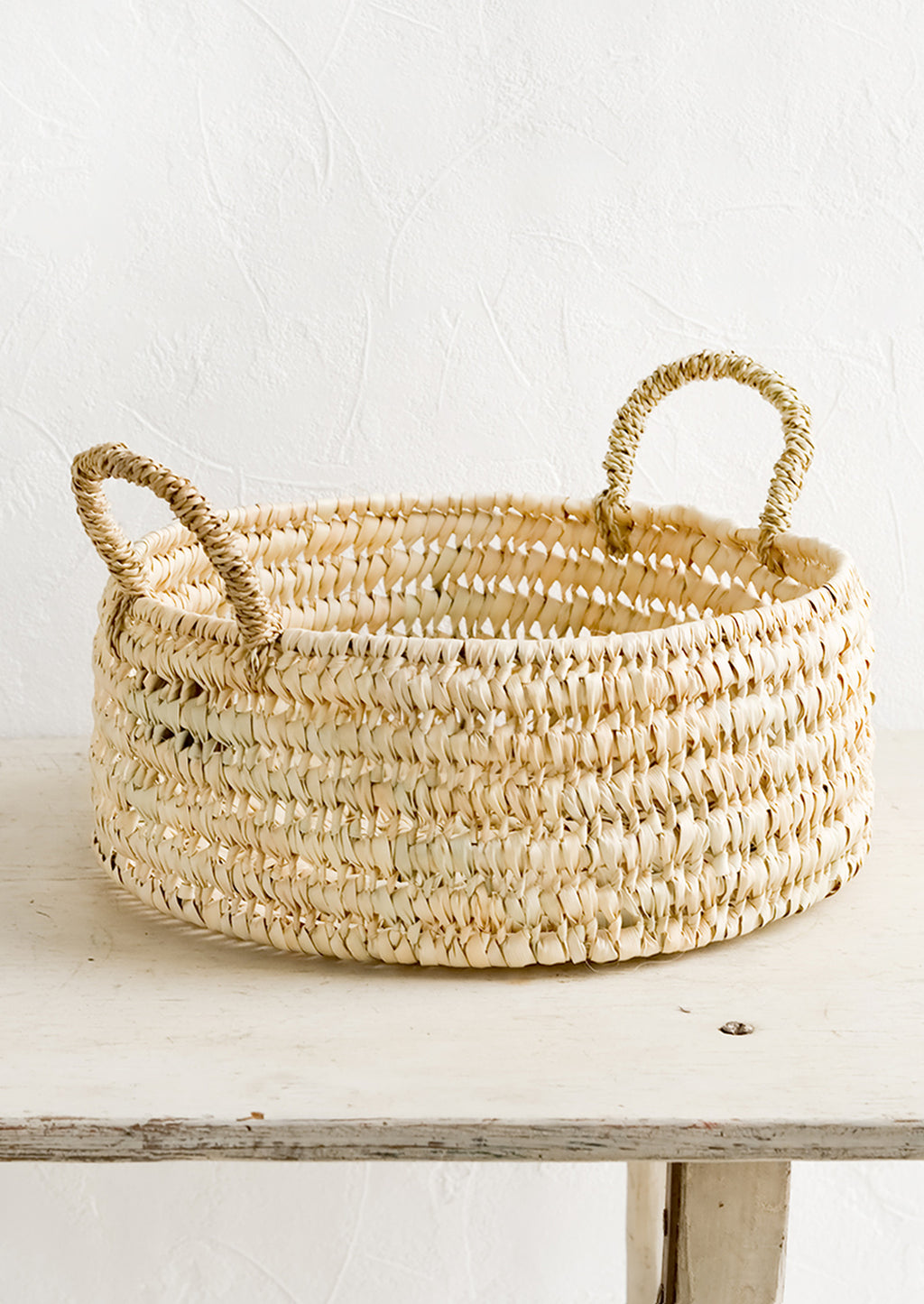 1: A round shallow storage basket made from dried palm leaf.