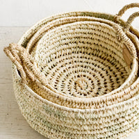 2: Three round palm leaf storage baskets in incremental sizes nested together.