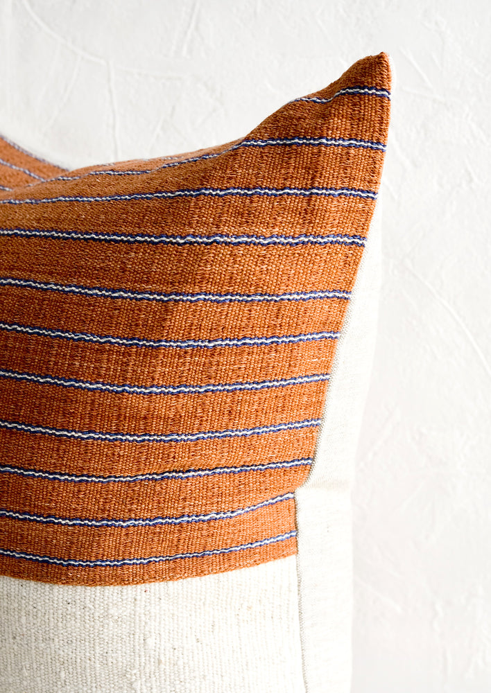 3: A throw pillow with top half in rust & indigo striped fabric and natural linen back.