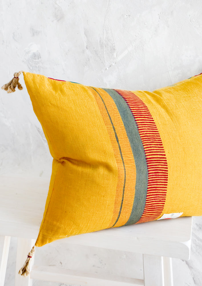 4: Back of lumbar throw pillow in mustard with block print stripe detail in red and green