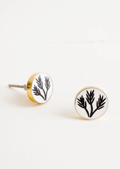 Round drawer knobs with white background and black leaf print, surrounded by brass bezel