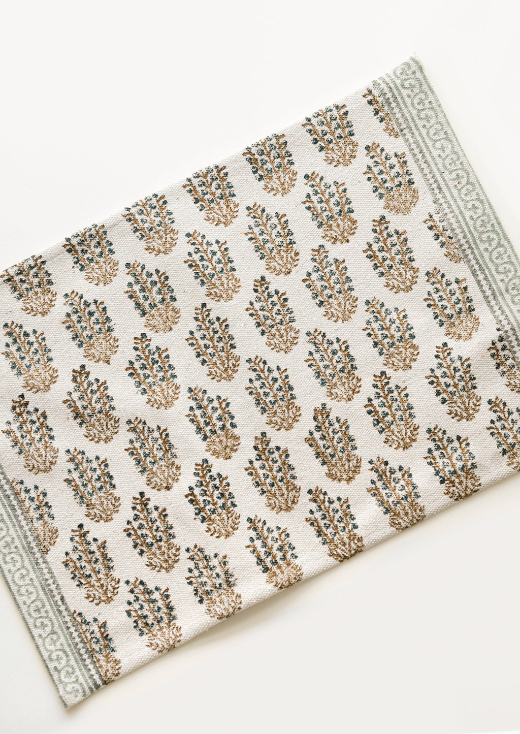 3: An ivory rectangular cotton placemat with green floral pattern.