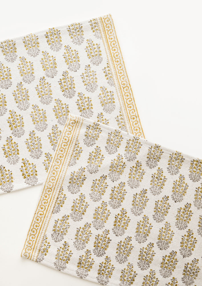 Mustard Multi: Two ivory rectangular cotton placemats with yellow floral pattern.