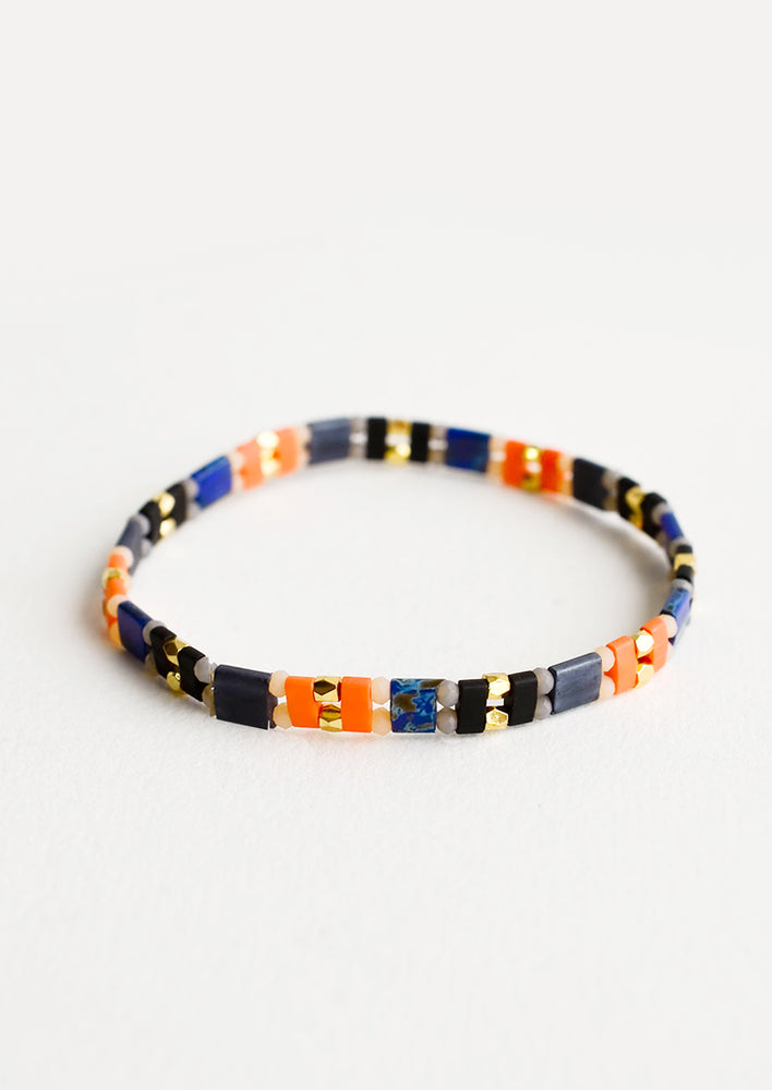 1: Bracelet featuring flat beads interspersed with gold bead on an elastic cord.