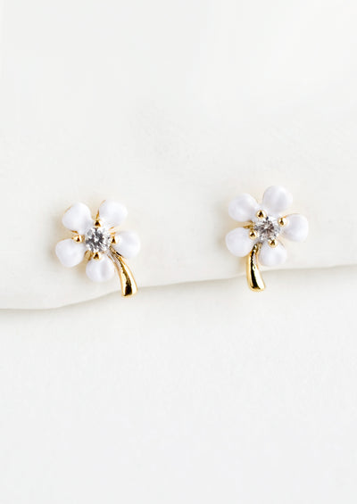 A pair of small gold stud earrings with white enamel flower and crystal center.