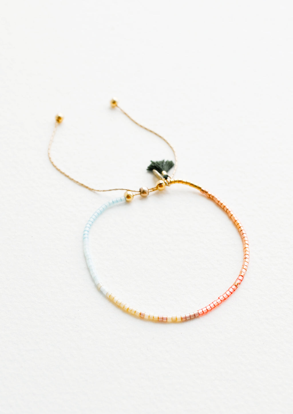 Copper / Sky Blue / Maize: Delicate bracelet of glass beads in a gradient from pale blue to deep rust on a thin gold chain.