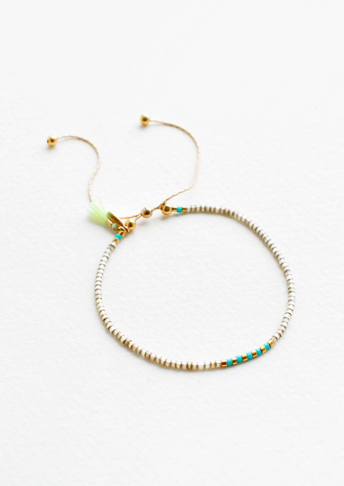 Khaki / Turquoise: Delicate bracelet of gray glass beads with alternating turquoise and gold beads at center on a thin gold chain.