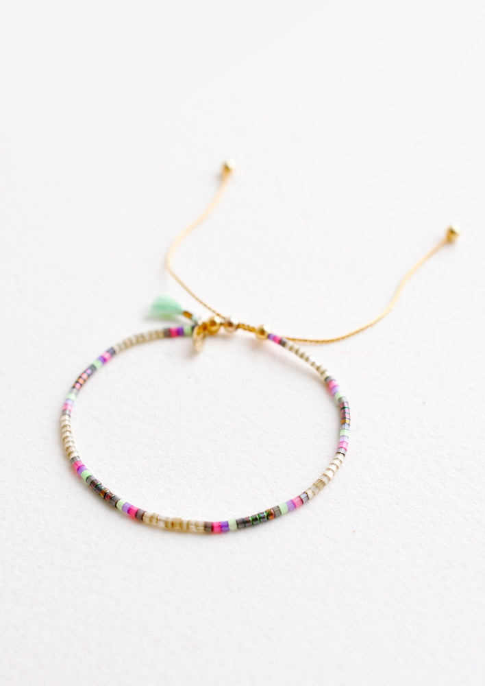 Delicate bracelet of gray glass beads with regularly spaced sections of pink and green beads on a thin gold chain.