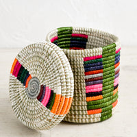 5: A small, round lidded basket made from woven sweetgrass on a table with lid askew.