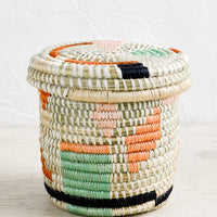Flora Multi: A small, round lidded basket made from woven sweetgrass with geometric pastel pattern.