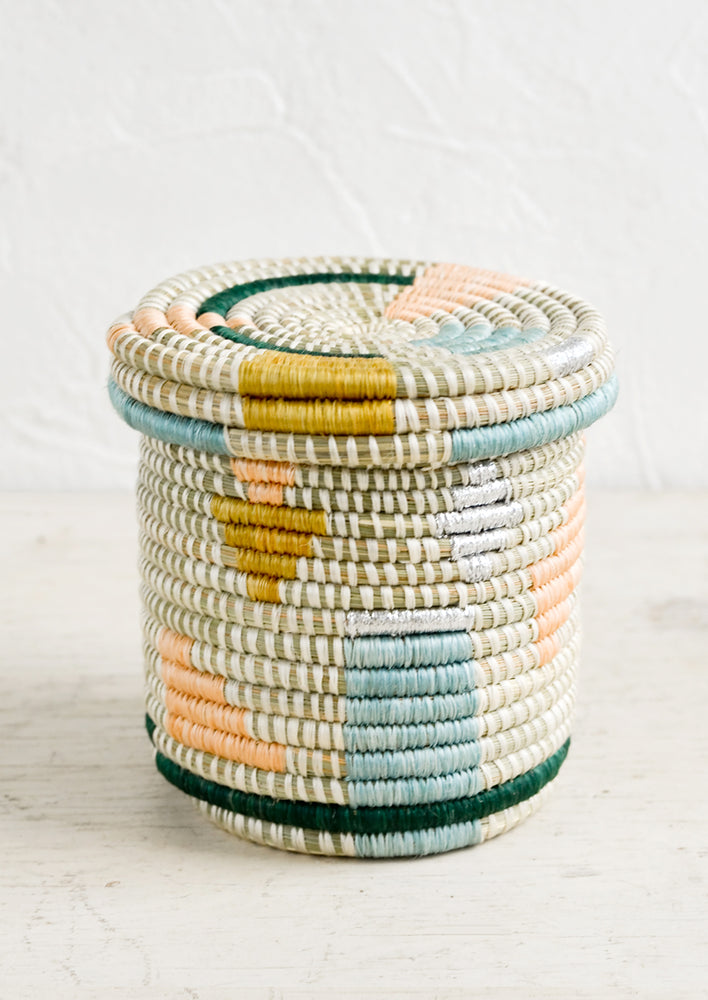 Pastel Multi: A small, round lidded basket made from woven sweetgrass with geometric pastel and metallic pattern.