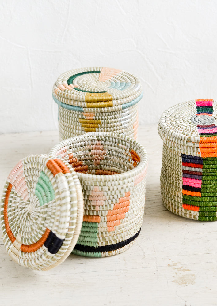 2: Assorted lidded woven baskets in a mix of colors and patterns.