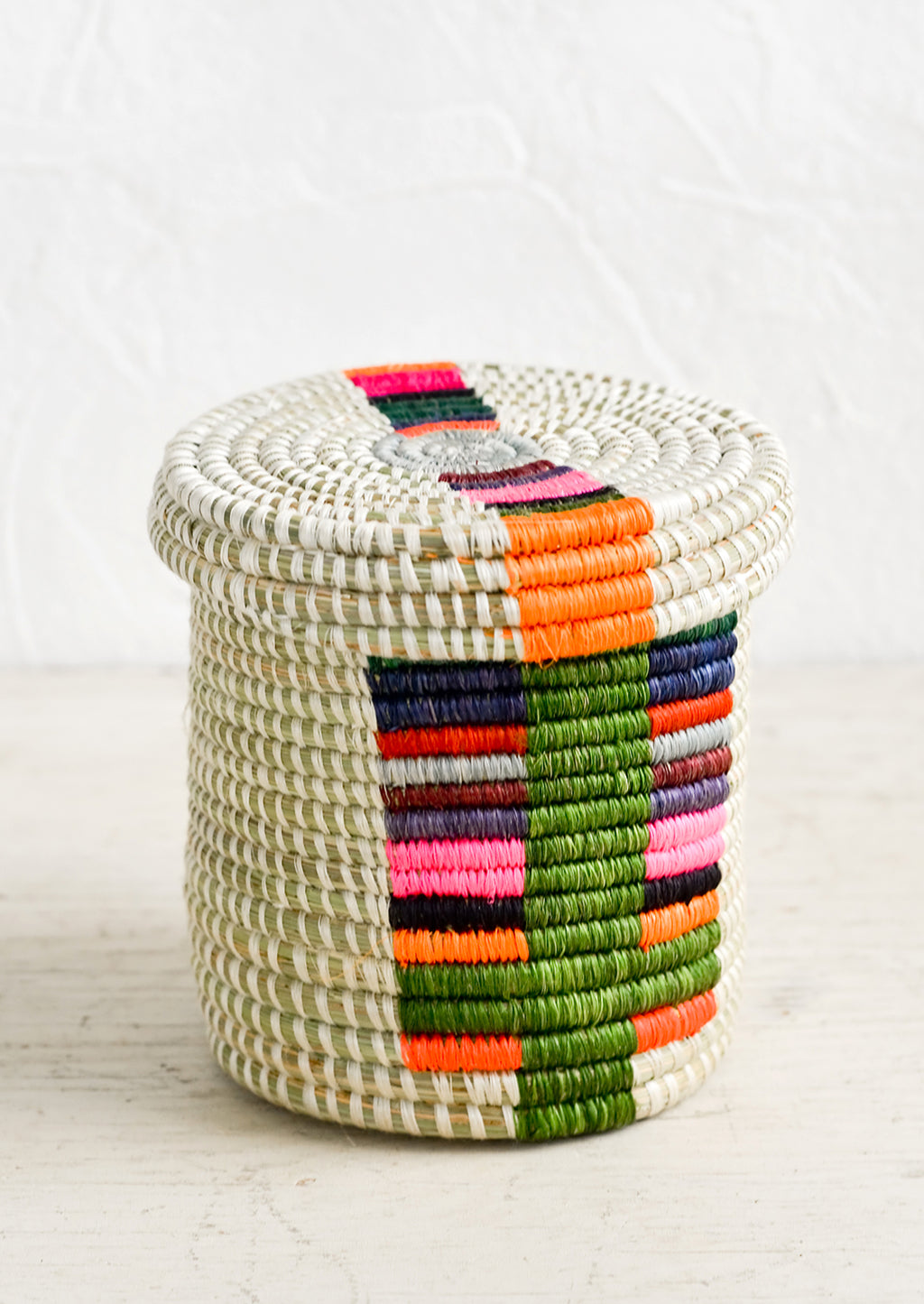Chroma Multi: A small, round lidded basket made from woven sweetgrass with colorful line pattern.