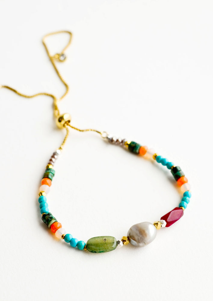 Gold chain bracelet with one pearl flanked by stone beads of blue, orange, green, and maroon.