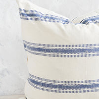 2: A large, square-shaped throw pillow in cream cotton with horizontal embroidered blue stripes.