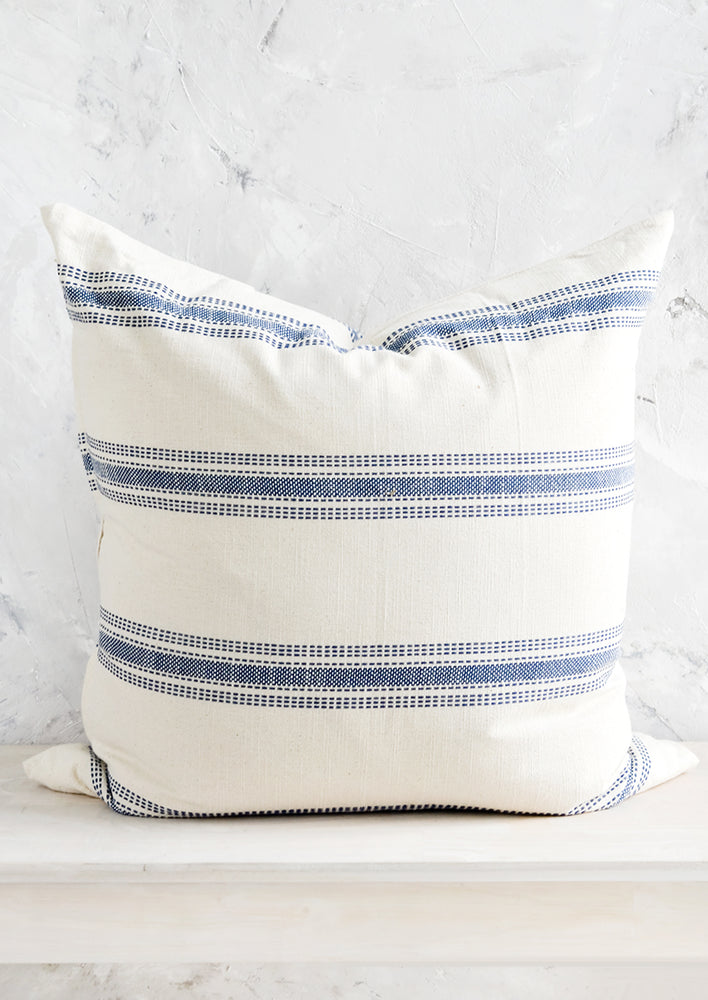 1: A large, square-shaped throw pillow in cream cotton with horizontal embroidered blue stripes.