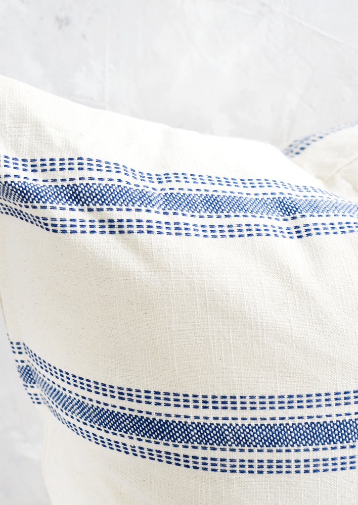 4: Blue embroidered stripe detailing on cream colored cotton.