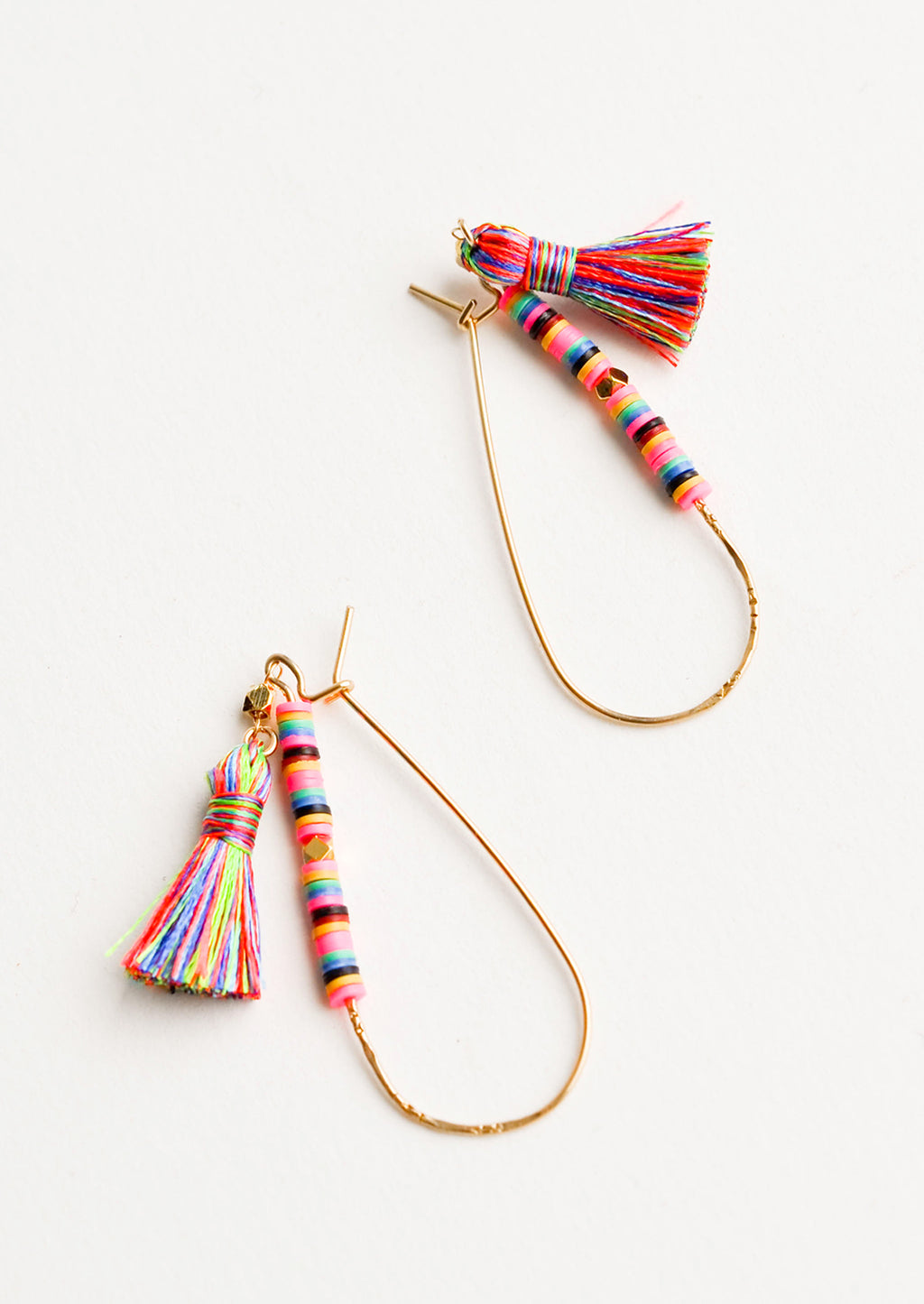 1: Thing gold teardrop earrings with bright multicolored beading and tassel on one half.