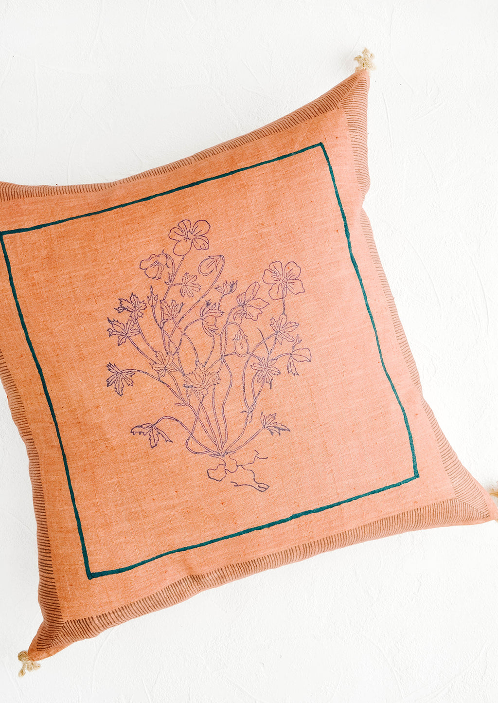 1: Decorative square-shaped throw pillow in clay brown linen with framed, block printed floral print.