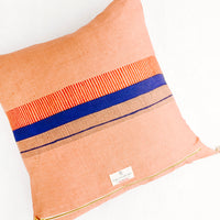 2: Back of throw pillow featuring block printed red and blue stripes on clay brown linen
