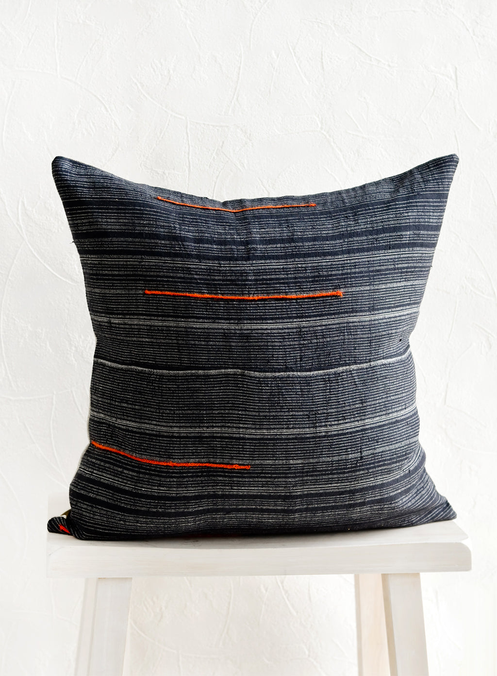 2: A square throw pillow made from dark blue fabric with grey stripes and embroidered orange lines.