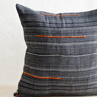1: A square throw pillow made from dark blue fabric with grey stripes and embroidered orange lines.