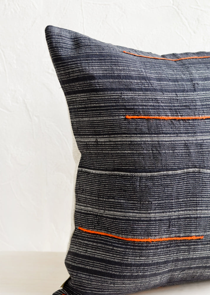 3: A square throw pillow made from dark blue fabric with grey stripes and embroidered orange lines.