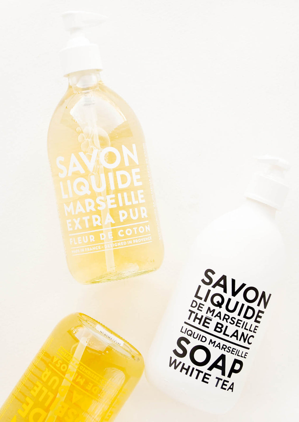 "Mimosa: Three glass soap bottles laid flat to display text reading ""savon liquide de Marseille."""