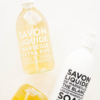 "Cotton Flower: Three glass soap bottles laid flat to display text reading ""savon liquide de Marseille."""