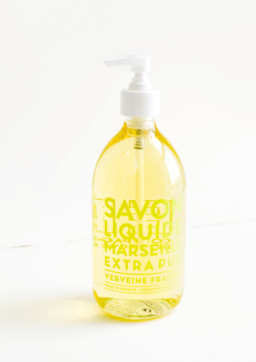 4: A clear glass soap bottle with pale yellow interior liquid, lime green text, and a white plastic dispenser.