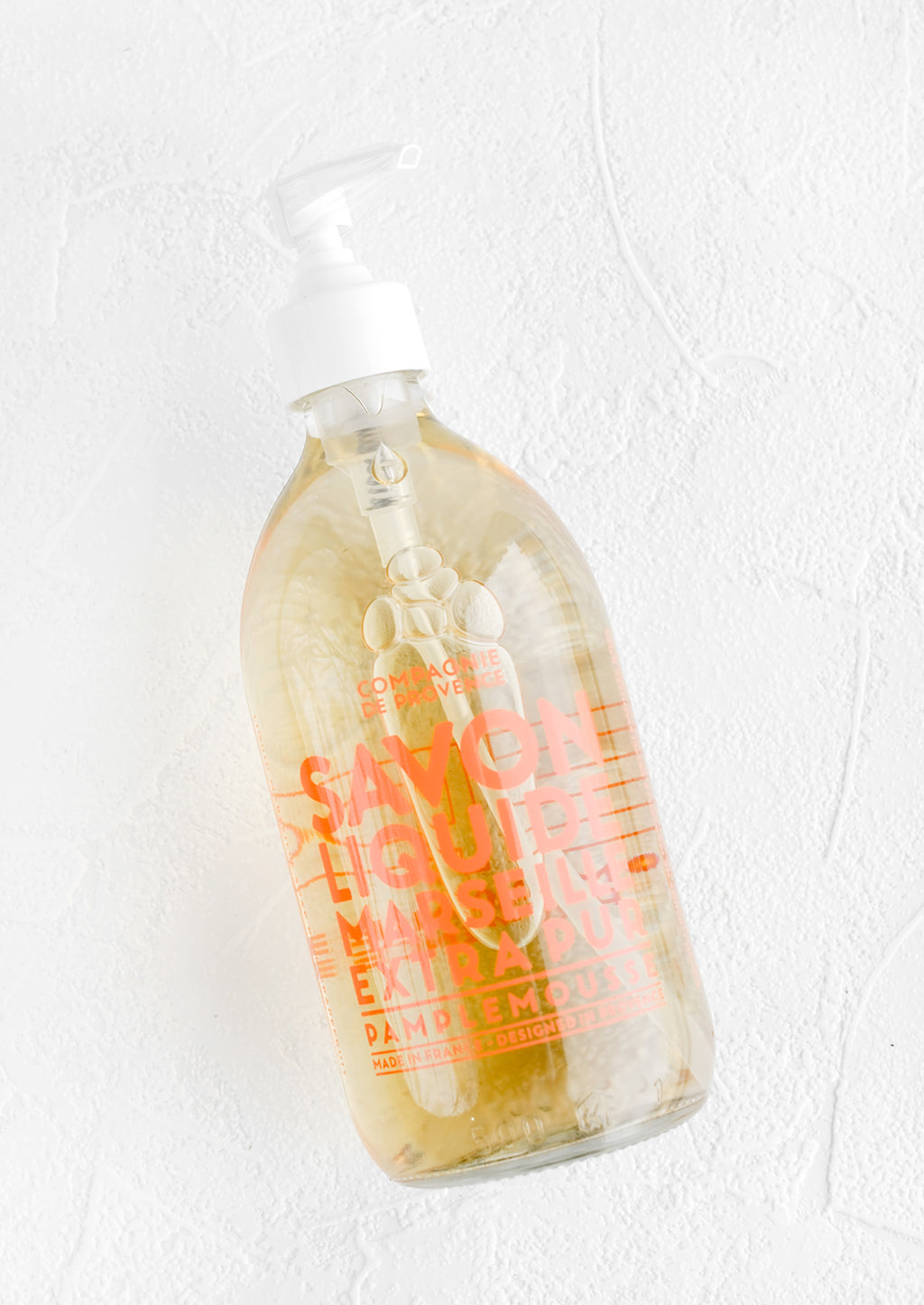 Grapefruit: A clear glass soap bottle with bold orange text printed on bottle