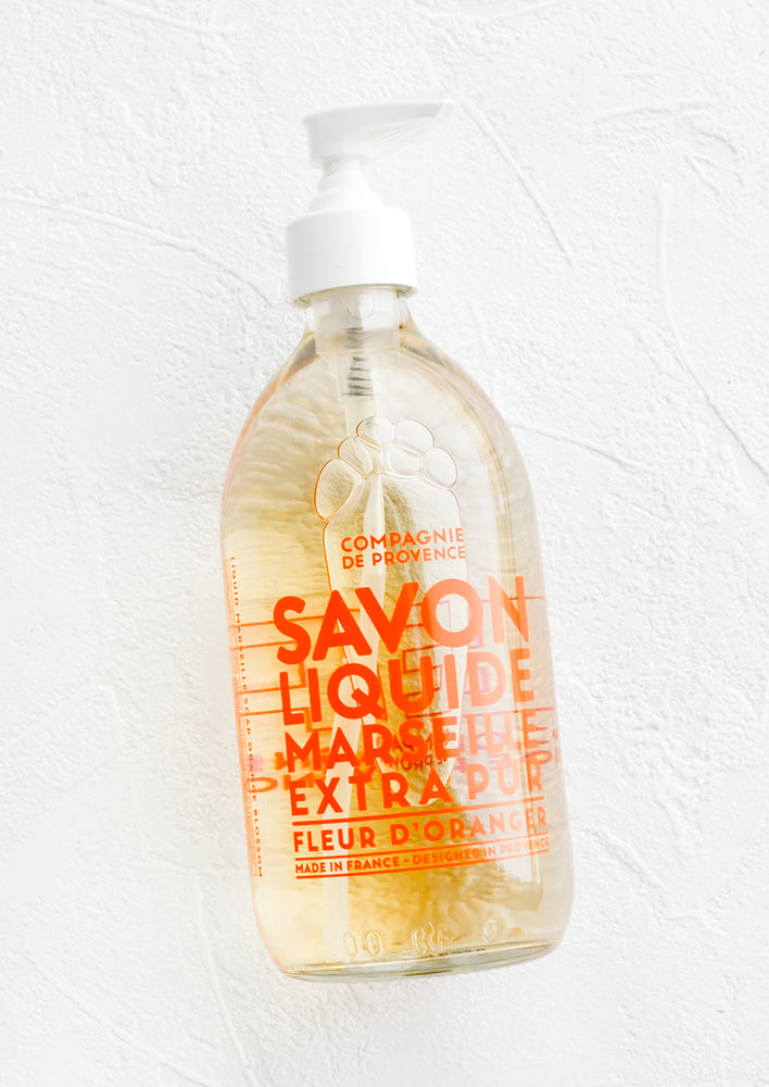 Orange Blossom: A clear glass soap bottle with bold orange text printed on bottle