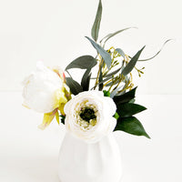 1: Small and round mini ceramic vase in white shown with floral arrangement