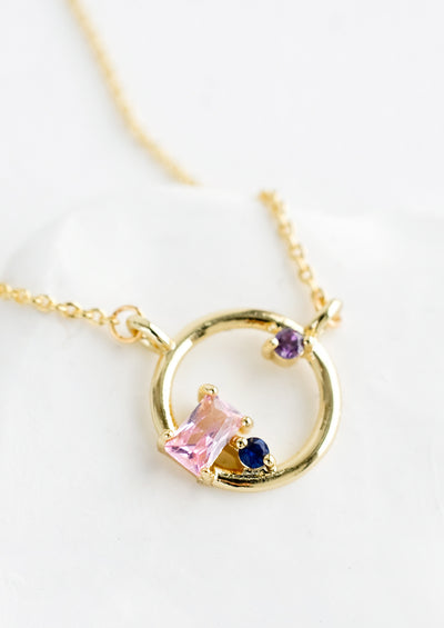 A gold necklace with delicate chain and circular charm with colored crystal detail.