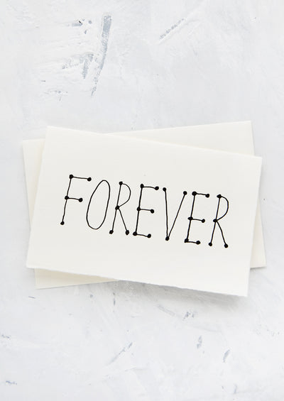 "A letterpress printed greeting card made from handmade paper with ""FOREVER"" printed in black letters"