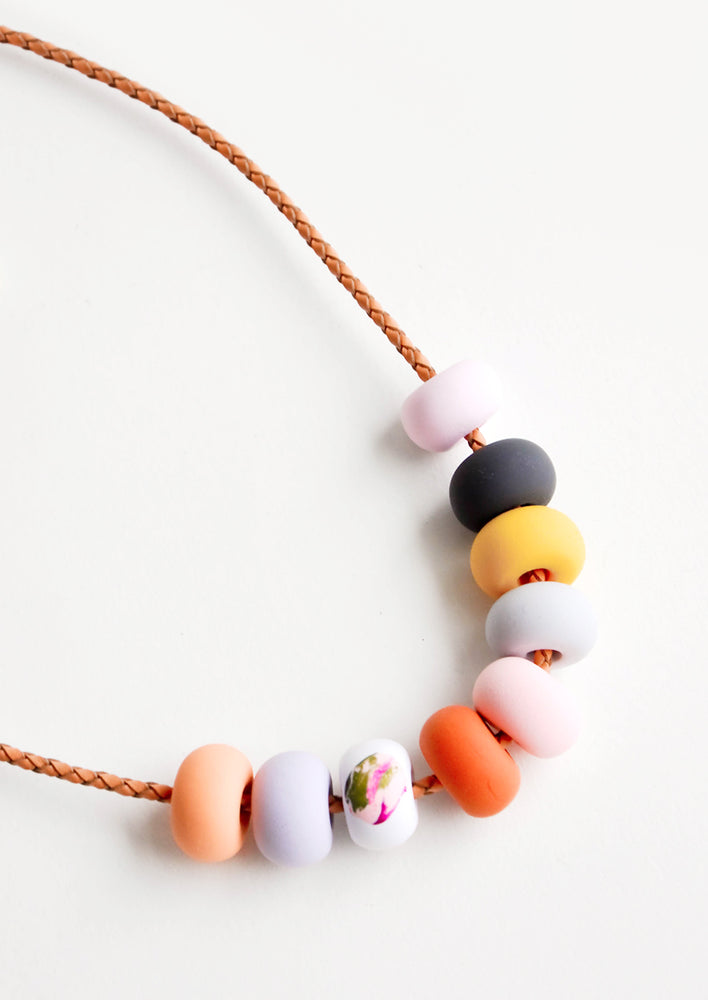 3: Close up of necklace with nine rounded clay beads in pink, navy, yellow, red, and orange.