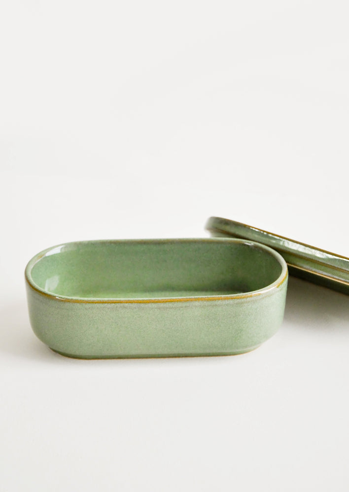 2: Oblong oval ceramic green Container with lid lying by its side.