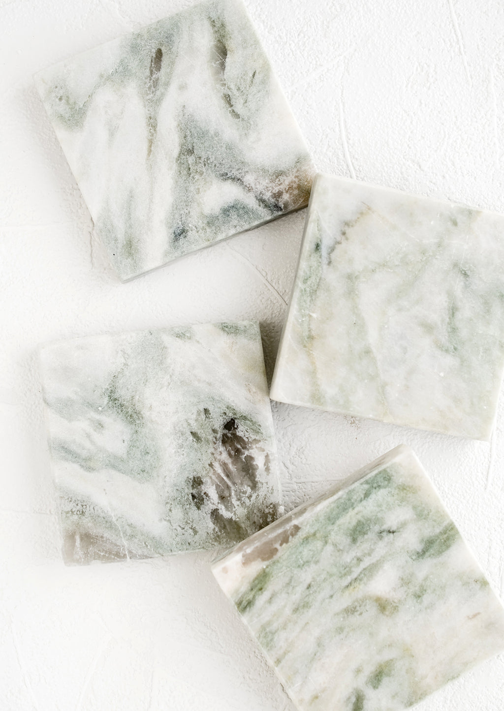 1: Four square marble coasters with variegated tones of green, white and grey.